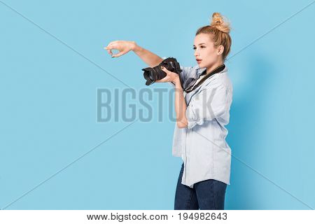 Woman Blonde Photographer Shows How To Pose To Somebody. Model Isolated On A Blue Background With Co