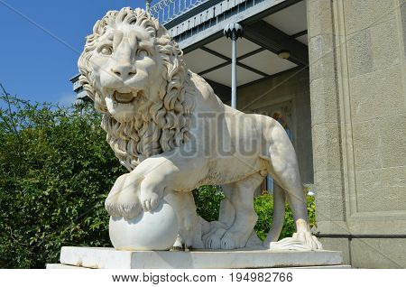 sculpture of a snarling marble lions resting on the ball