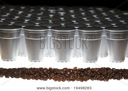 Row of roasted coffee beans in front of a line of plastic cups, angular view