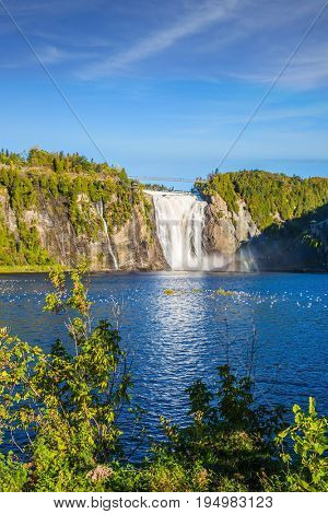 The blue lake and waterfall Montmorency in Montmorency Falls Park, in vicinities Quebec. Flock of water birds resting in water. The concept of active and cultural tourism