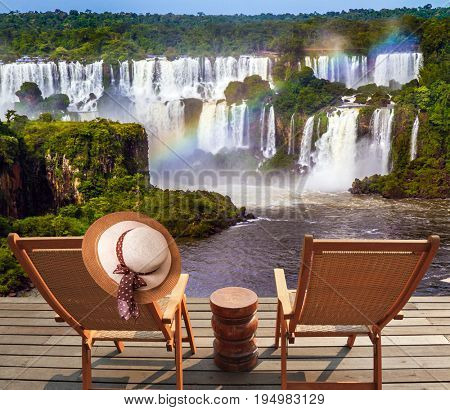 Incredible exotic waterfalls of Iguazu in South America. Two comfortable wooden chaise lounges face waterfalls. On one hangs an straw female hat. Concept of exotic and eco-tourism