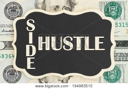 Making money with your side hustle Side Hustle text on chalkboard on USA twenty dollar bills