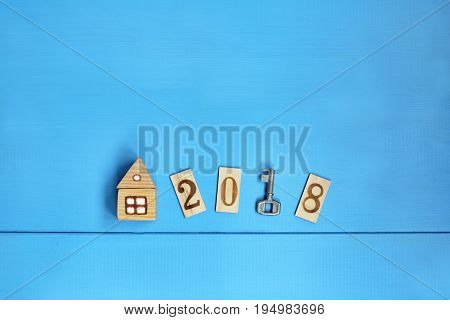 Flat lay with key home and wooden numbers on the blue table top view / Detached house in 2018