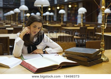 Young attractive woman sitting at desk in old university library studying books.