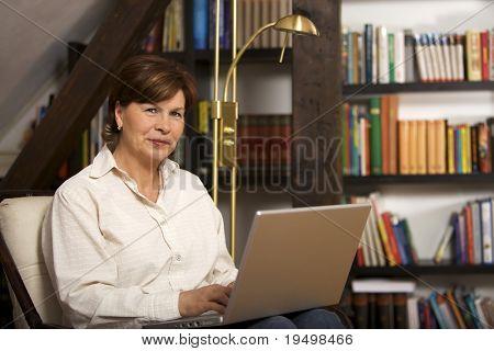 Mujer senior moderna enfrete de la estantería y trabajando en equipo portátil.