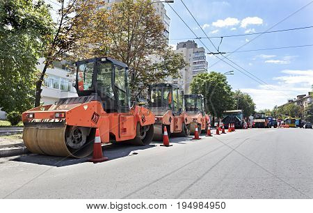 Among the summer noon three heavy road vibrating roller compactors and other equipment are ready for repair of the road in a modern city