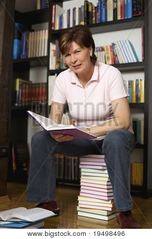 Smiling senior woman sitting on book stack in front of bookshelf at home and reading a book.