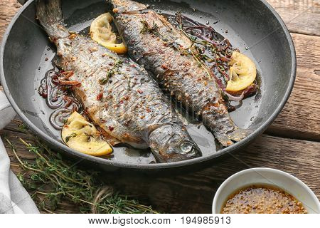 Frying pan with tasty trout fish on wooden background