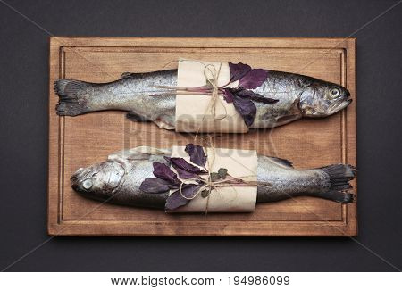 Wooden board with two fresh trout fish wrapped in paper, on black background