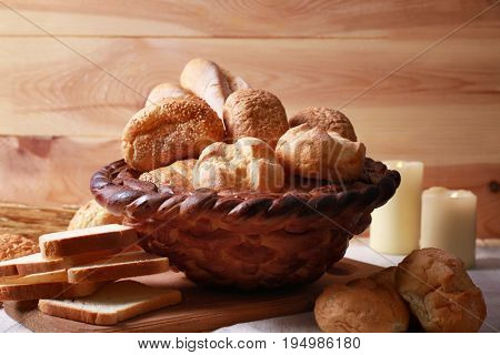 Baked basket and variety of bread on wooden background
