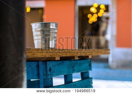 Cubo metálico en día de verano con bokeh, orange teal