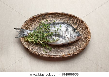Wooden plate with fresh dorado fish on light background