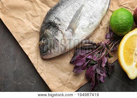 Fresh dorado fish, red basil and citrus fruits on gray background
