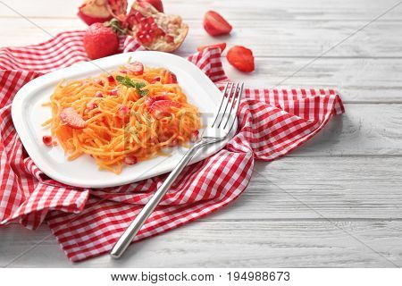 Plate with yummy carrot strawberry salad with pomegranate seeds on cute red checkered napkin