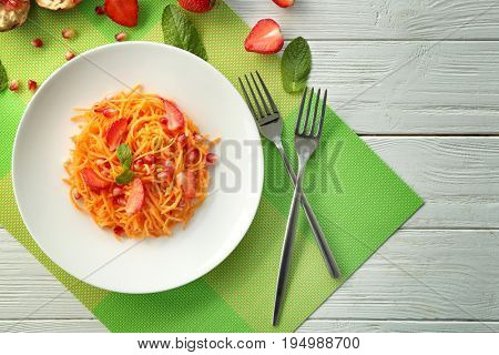 White round plate with yummy carrot strawberry salad on green napkin