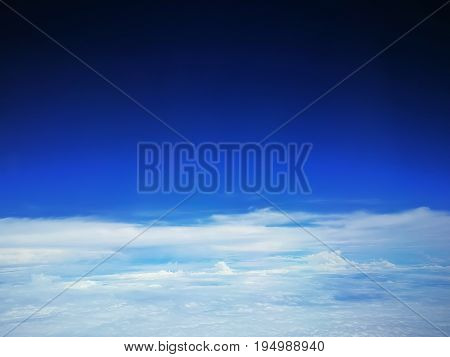 Beautiful shading blue sky over white cloud separated by the horizon. View from airplane window. Natural background. Concepts of freedom, peaceful, heaven, separate.