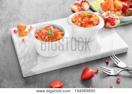 Cute white bowls with yummy carrot strawberry salad on marble board