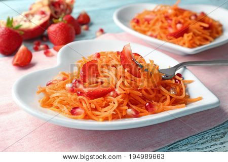 Yummy carrot salad with strawberry and pomegranate seeds on heart-shaped plate