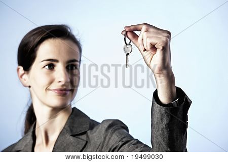 The Key to Success concept: Portrait of business woman holding key between fingers, focus on key, blue background.