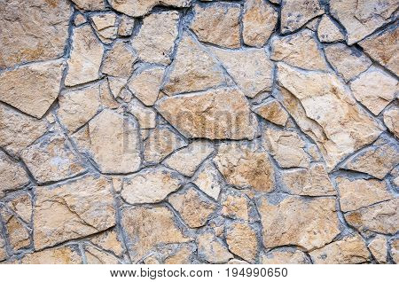 A Background With Wall Covered By Brown Flat Stones With Sharp Edges. The Gap Between Stones Filled