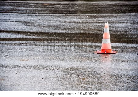A Road Cone With Broken Top Placed On Asphalt On The Right Side Of The Photo. Cone Reflects In The W