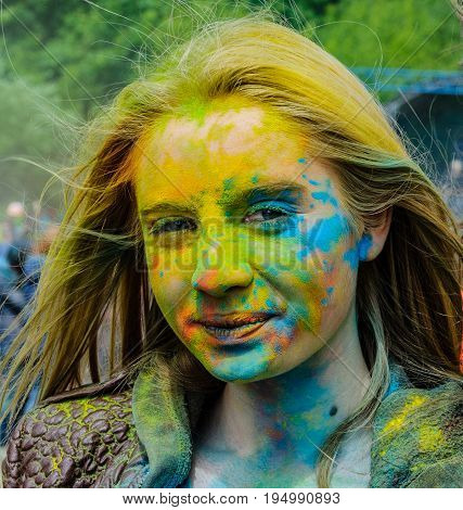 Moscow, Russia - June 3, 2017: Face of young blonde girl, covered different colors by paints Holi at a colorful festival. Yellow, blue, green splashes of powder paint.