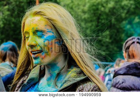 Moscow, Russia - June 3, 2017: Portrait of young blonde girl, powdered different colors by paints Holi at a colorful festival. Yellow, blue, green vibrant splashes of powder paint.