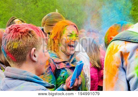 Moscow, Russia - June 3, 2017: Happy laughing red-haired girl in the epicenter of a colorful splash at the Holi festival. Traditional Indian festival turned into a fun event in many countries