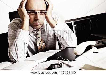 Bezorgd zakenman achter bureau vol met boeken en papers worden overladen met werk.