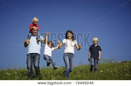 Šťastná rodina pěti chůzi v louce a vyhazoval dcera.