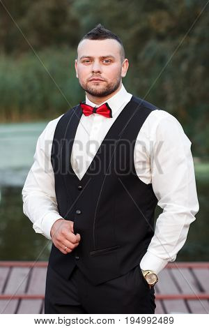 Young stylish man in a waistcoat vertical portrait of the groom portrait on a background of nature the river and the pier look at the camera hand with golden watch. Business concept.
