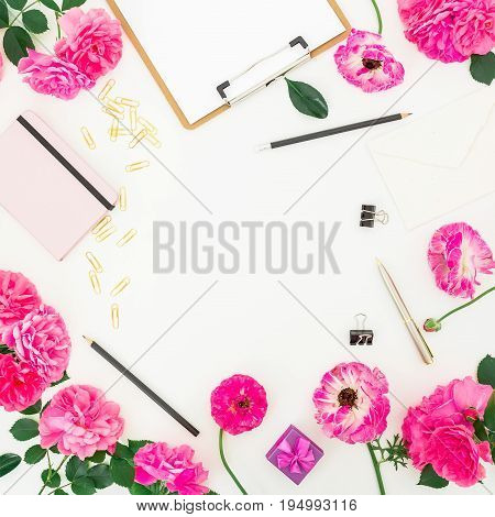 Pink feminine workspace with clipboard, notebook, purple roses and accessories on white background. Flat lay, top view. Blogger of freelancer workspace