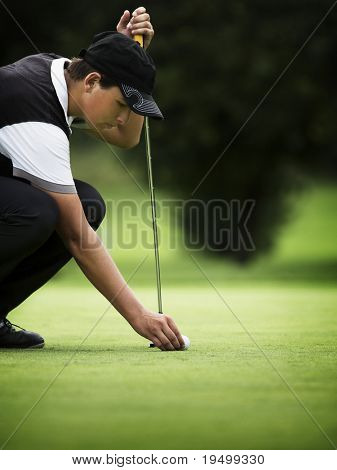 Young golf player squatting to put down ball at green.