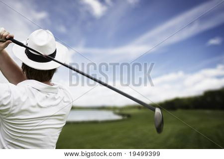 Close-up of male golf player with hat teeing-off at beautiful golf course.