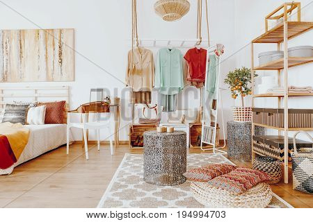 Bright spacious room with colorful clothes and decorations in boho style