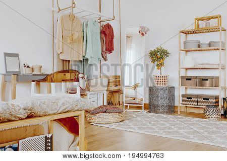 Creative wardrobe with colorful elegant clothes and white mirror in the corner of the bedroom