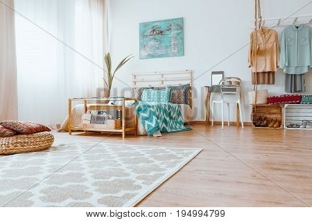 Bright tidy colorful bedroom with big carpet and modern painting