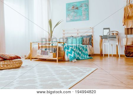 Wooden bed with blue and white blanket and decorative cushions