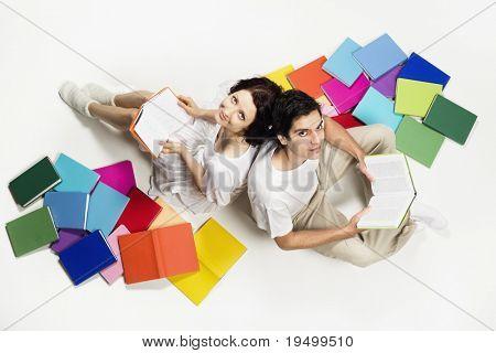 Schöne Mädchen und jungen sitzen auf Boden mit bunten Bücher und lesen, nachschlagen, isolated on white