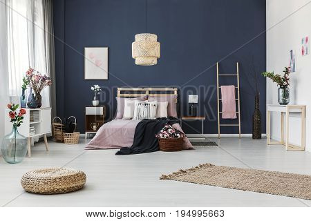 Painting hanging on dark blue wall in cozy bedroom with fresh flowers