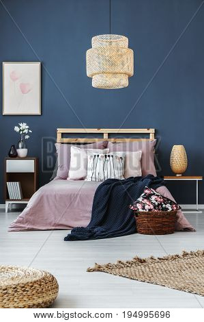 Dark blue blanket thrown on the bed with bright stylish bedding