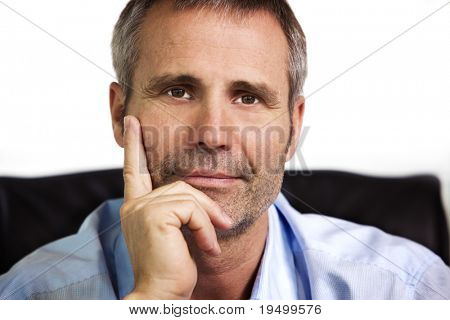 Close up portrait of smiling businessman in blue shirt looking straight and resting chin on  hand, isolated on white background.