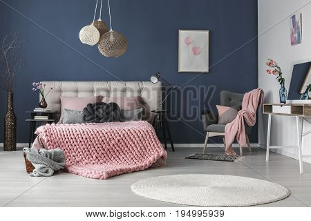 Dark grey comfy armchair with cushion and pink blanket in the corner of the room