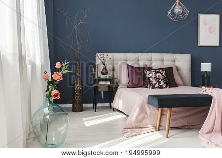 Spacious dark walled room with pastel pink bed and windows
