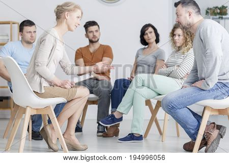 Talking with psychologist during group psychotherapy meeting