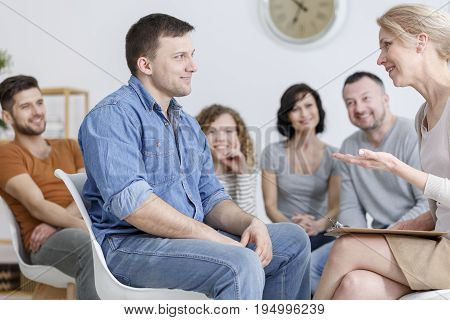 Smiling man consulting his psychotherapist during group therapy session