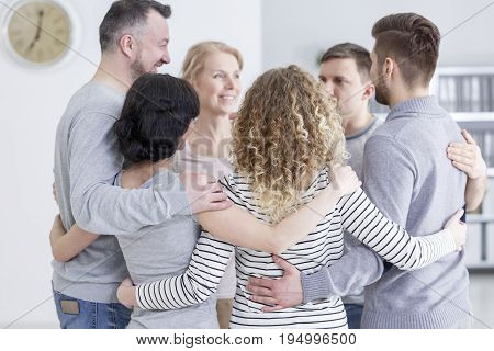 People having group hug during therapy in rehab