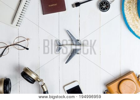 Travel accessories and gadget on whtie wooden with Toy plane