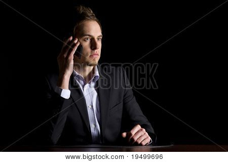 Handsome young business executive in dark suit sitting at office desk talking on mobile-phone, low-key image isolated on black background.