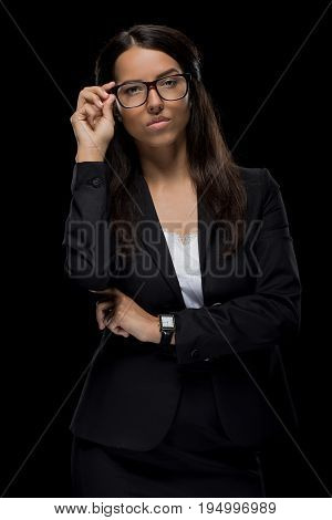 Beautiful Confident Businesswoman Posing In Eyeglasses And Black Suit, Isolated On Black